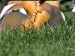 Lying in the grass, great view of feet & legs